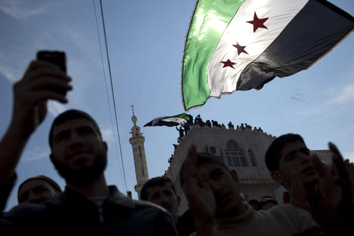 FILE - In this Friday, March 2, 2012 file photo, men hold revolutionary Syrian flags during an anti government protest in a town in north Syria. More than two years into Syria's civil war, the once highly-centralized authoritarian state has effectively split into three distinct parts, each boasting its own flags, security agencies and judicial system. (AP Photo/Rodrigo Abd, File)