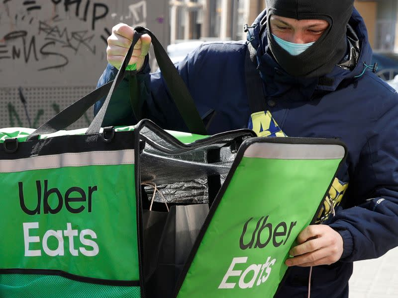 FILE PHOTO: An Uber Eats food delivery courier closes a bag with an order in central Kiev