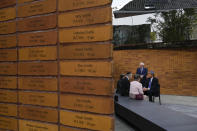 """Name stones are seen in the foreground as King Willem-Alexander, right, talks to survivors and relatives after officially unveiling a new monument in the heart of Amsterdam's historic Jewish Quarter on Sunday, Sept. 19, 2021, honoring the 102,000 Dutch victims of the Holocaust. Designed by Polish-Jewish architect Daniel Libeskind, the memorial is made up of walls shaped to form four Hebrew letters spelling out a word that translates as """"In Memory Of."""" The walls are built using bricks each of which is inscribed with the name of one of the 102,000 Jews, Roma and Sinti who were murdered in Nazi concentration camps during World War II or who died on their way to the camps. (AP Photo/Peter Dejong)"""