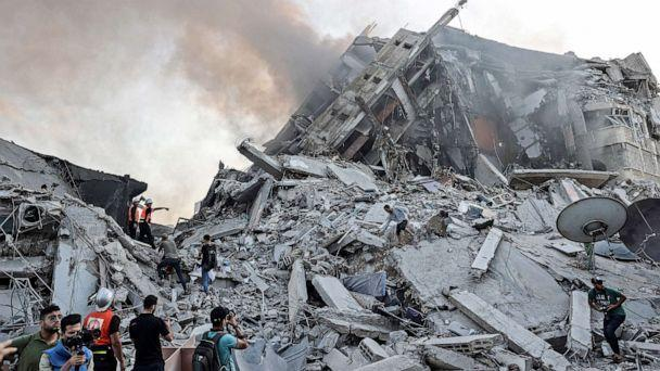 PHOTO: People gather in front of the debris of Al-Sharouk tower that collapsed after being hit by an Israeli air strike, in Gaza City, on May 12, 2021. (Mahmud Hams/AFP via Getty Images)