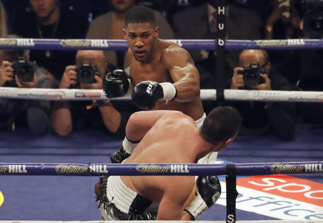 FILE - In this March 31, 2018, file photo, Britain's Anthony Joshua, rear, tries to hit New Zealand's Joseph Parker during their heavyweight title bout in Cardiff, Wales. In June, the World Boxing Association ordered Joshua sign to fight Alexander Povetkin or have his title stripped away. He signed, destroying chances of a Deontay Wilder-Joshua fight in 2018. Wilder said if Joshua wanted the fight to happen, it would be happening. (AP Photo/Frank Augstein, File)