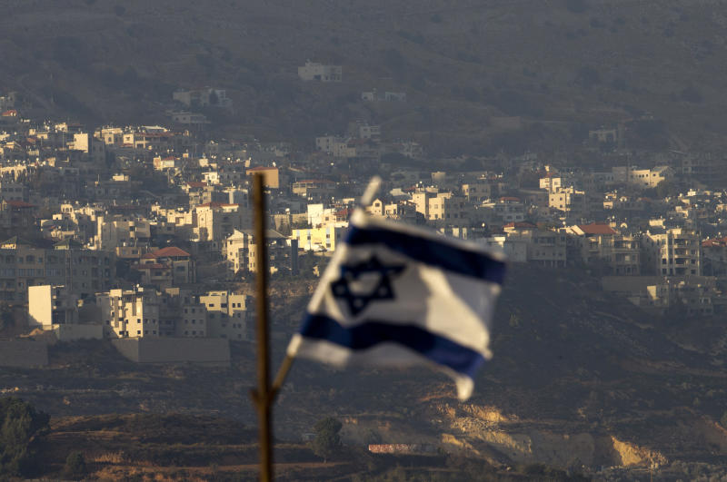"""FILE - In this file photo dated Thursday, Oct. 11, 2018, an Israeli flag in front of the village of Majdal Shams in the Israeli-controlled Golan Heights. Syria slammed President Donald Trump's abrupt declaration that Washington will recognise Israel's sovereignty over the Israeli-occupied Golan Heights, saying Friday March 22, 2019, the statement was """"irresponsible"""" and a threat to international peace and stability. (AP Photo/Ariel Schalit, FILE)"""