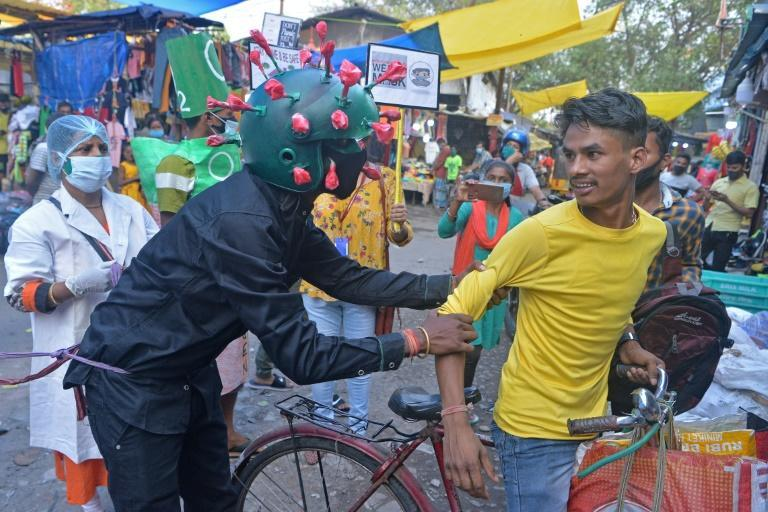 A man wearing a Covid-19 outfit urges people to follow safety protocols during an awareness drive held in Siliguri, India