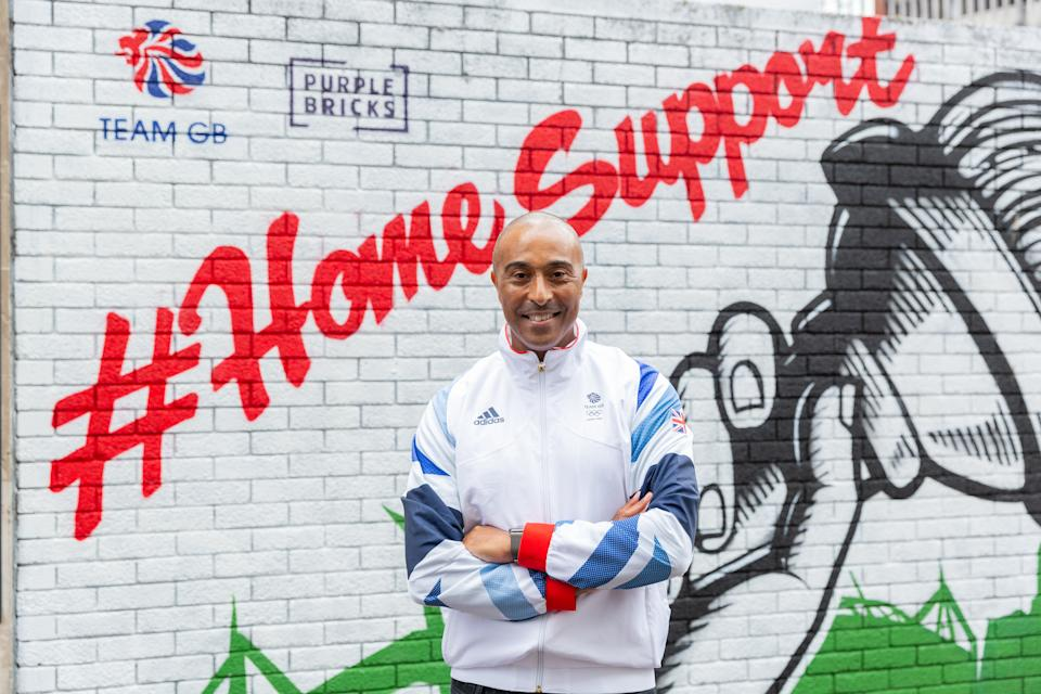 Jackson poses in front of the mural he unveiled as part of the Purple Bricks Home Support campaign in Cardiff.