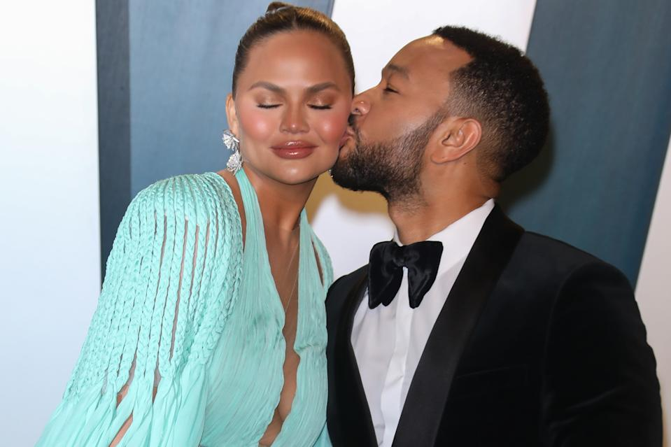 Chrissy Teigen gets a kiss on the cheek from husband John Legend at the 2020 Vanity Fair Oscar Party at Wallis Annenberg Center for the Performing Arts on February 09, 2020 in Beverly Hills, California