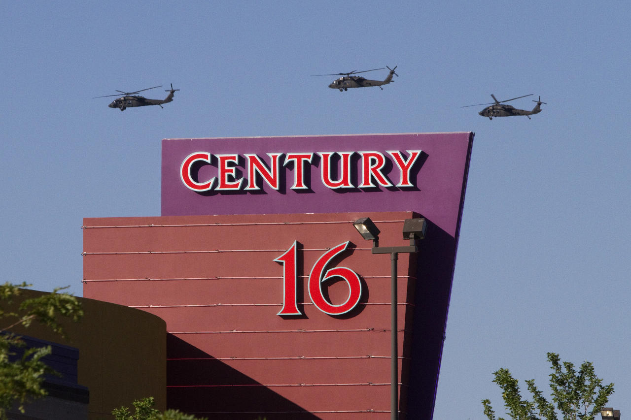 """Three helicopters make a flyover of the Century Theater on Saturday, July 21, 2012 in Aurora, Colo. Twelve people were killed and dozenswere injured in the attack early Friday at the packed theater during a showing of the Batman movie, """"Dark Knight Rises."""" Police have identified the suspected shooter as James Holmes, 24. (AP Photo/Barry Gutierrez)"""