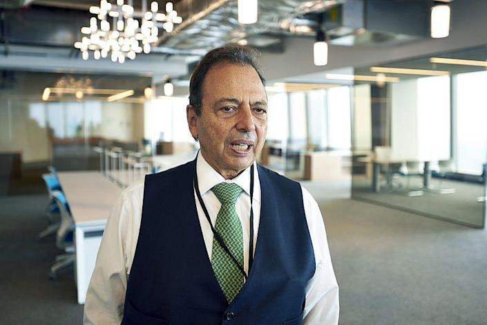 Douglas Durst, chairman of The Durst Organization, wears a white shirt and black waistcoat in a corporate meeting room.