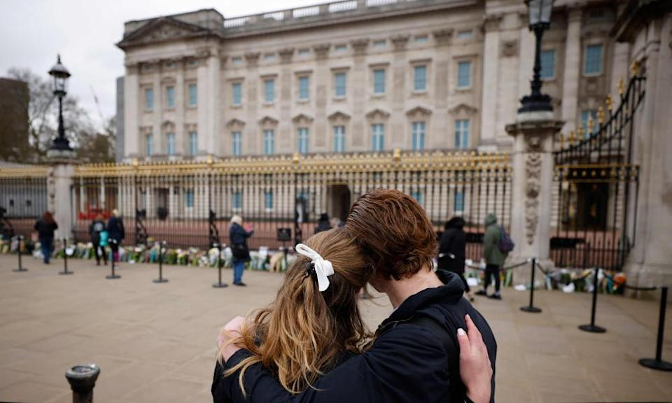 A couple watch as well-wishers leave floral tributes to Britain's Prince Philip.