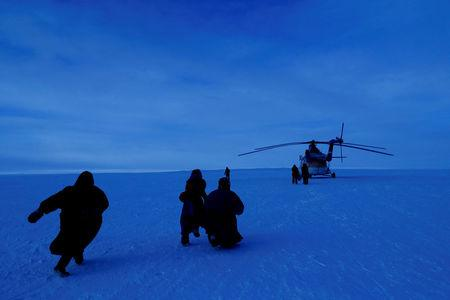 "Children from the indigenous community ""Yamb To"" (Long Lake) run to a helicopter carrying local electoral commission officials during the early voting in remote areas ahead of the presidential election, at a reindeer camping ground, about 450 km northeast of Naryan-Mar, in Nenets Autonomous District, Russia, March 1, 2018. REUTERS/Sergei Karpukhin"