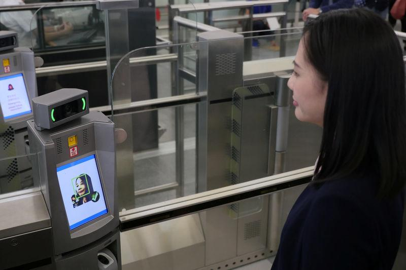 "A ""smart departure"" self-service machine scans a woman's face to authenticate her identity during a demonstration at airport in Hong Kong"