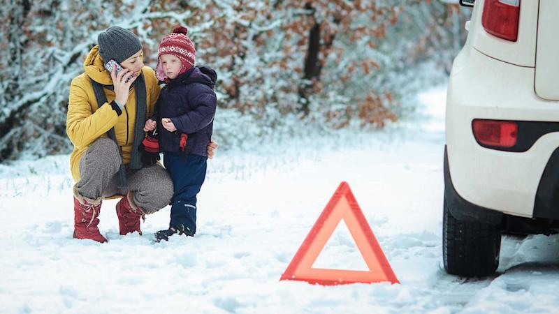 Winter car breakdown with mother and child by side of the road
