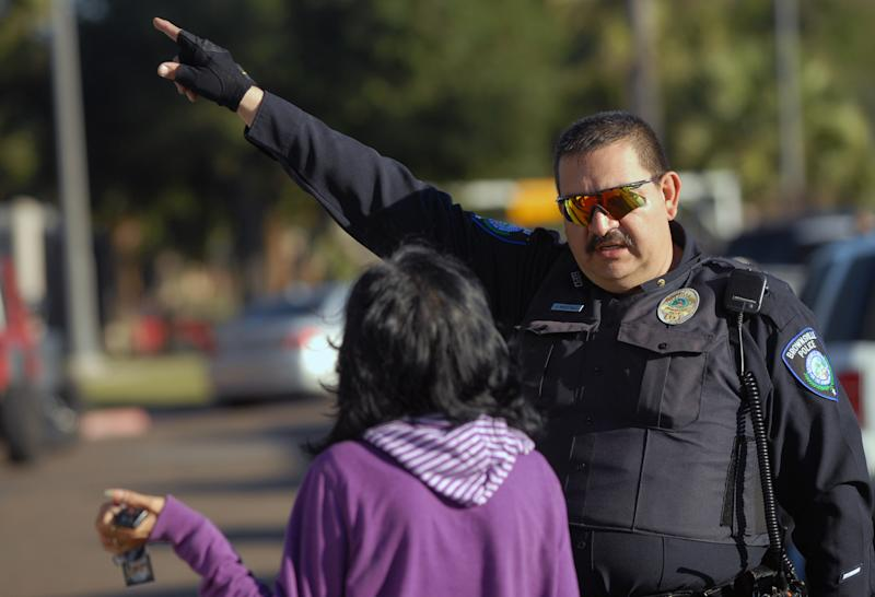 A Brownsville Police officer directs a parent to a building at Dean Porter Park in Brownsville,Texas, Wednesday, Jan. 4,2012. The park is across the street from Cummings Middle School,  where a 15-year-old student was shot and killed by Brownsville police at the school after he was seen brandishing a weapon inside the school. (AP Photo/The Brownsville Herald, Brad Doherty)