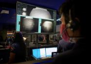 Members of NASA's Perseverance Mars rover team watch in mission control as the first images arrive moments after the spacecraft successfully touched down