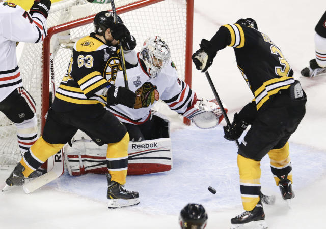 Boston Bruins center Patrice Bergeron (37) lines up the puck for a scoring shot against Chicago Blackhawks goalie Corey Crawford, rear, alongside Boston Bruins left wing Brad Marchand (63) during the second period in Game 4 of the NHL hockey Stanley Cup Finals, Wednesday, June 19, 2013, in Boston. (AP Photo/Charles Krupa)