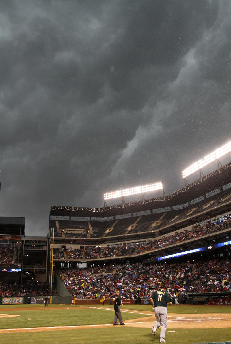 Home plate umpire Greg Gibson, left, and Oakland Athletics catcher Landon Powell (11) walk onto the field as storm clouds settle over the Texas Rangers Ballpark in Arlington in the fourth inning of a baseball game Wednesday, May 11, 2011, in Arlington, Texas. The game was rain delayed in the same inning. (AP Photo/Tony Gutierrez)