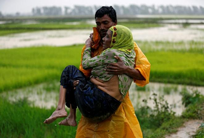 A local man carries an old Rohingya refugee woman as she is unable to walk after crossing the border, in Teknaf, Bangladesh