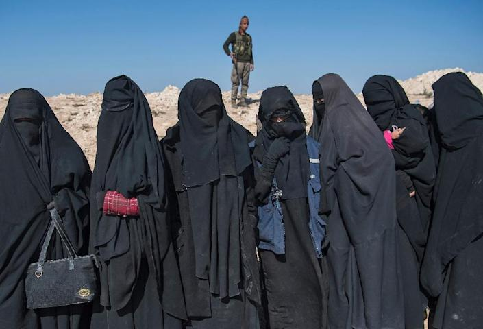 A fighter with the US-backed Syrian Democratic Forces (SDF) keeps watch near women who fled Islamic State group territory in Baghouz (AFP Photo/Fadel SENNA)