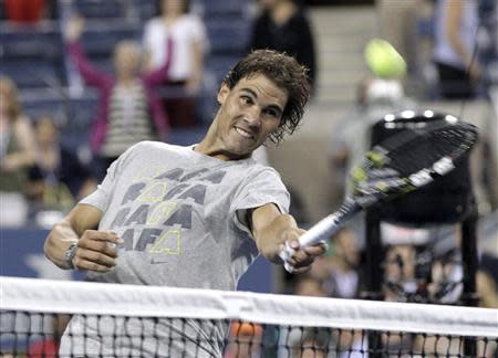 Rafael Nadal of Spain hits tennis balls into the crowd after defeating Rogerio Dutra Silva of Brazil at the U.S. Open tennis championships in New York, August 29, 2013. REUTERS/Shannon Stapleton