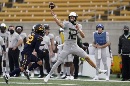 Oregon quarterback Tyler Shough (12) throws a pass as California safety Daniel Scott (32) closes in during the first half of an NCAA college football game in Berkeley, Calif., Saturday, Dec. 5, 2020. (AP Photo/Jeff Chiu)