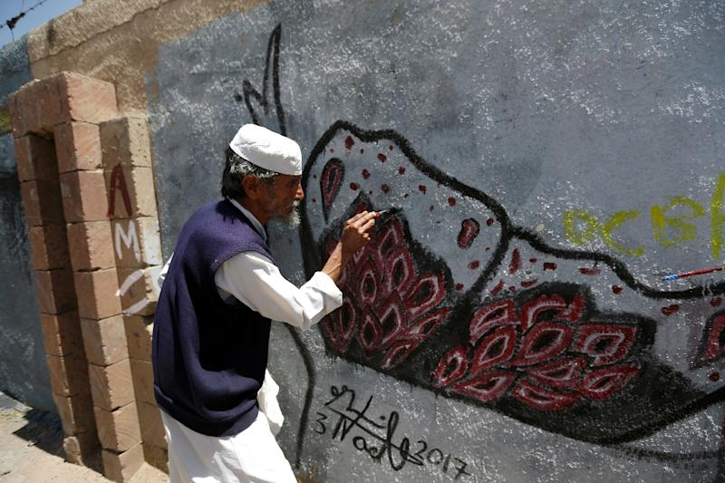 A man works on a mural on the southern wall of Sanaa University. (AFP Photo/Mohammed HUWAIS)