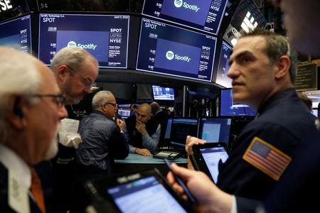 Traders await price updates of Spotify before the company's direct listing on the floor of the New York Stock Exchange in New York, U.S., April 3, 2018.  REUTERS/Lucas Jackson