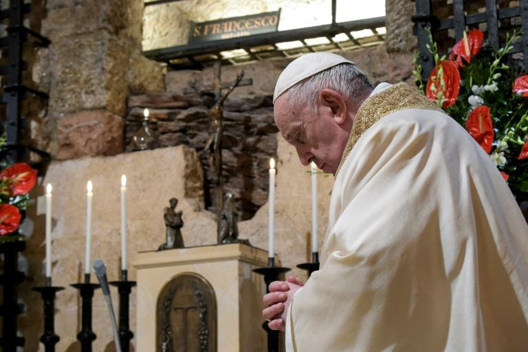 Pope Francis prays during mass at the tomb of Saint Francis in Assisi, during his first trip outside Rome in seven months