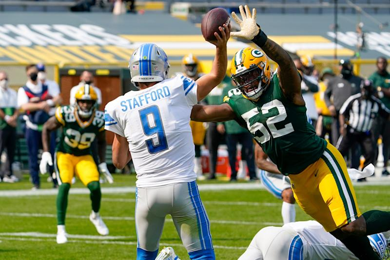 Detroit Lions' Matthew Stafford throws an interception to Green Bay Packers' Chandon Sullivan (39) during the second half of an NFL football game Sunday, Sept. 20, 2020, in Green Bay, Wis. Michigan alumni Rashan Gary (52) caused the pressure.