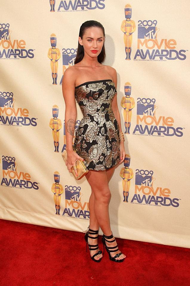 """<a href=""""http://movies.yahoo.com/movie/contributor/1808488000"""">MEGAN FOX</a>  Grade: B-  Her ultra-mini with shiny gold floral print isn't atrocious, but her ridiculously high heels are an ankle sprain waiting to happen, and the slicked back hair is severely unflattering."""