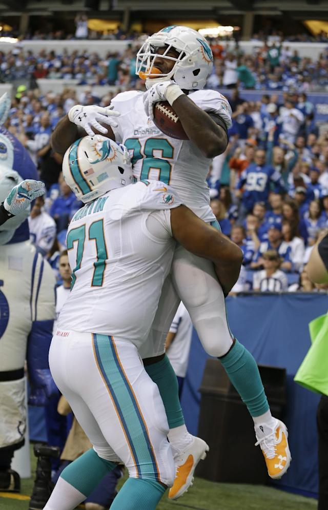 Miami Dolphins' Lamar Miller (26) celebrates with Jonathan Martin after Miller ran for a 10yard touchdown run in the first half an NFL football game against the Indianapolis Colts Sunday, Sept. 15, 2013, in Indianapolis. (AP Photo/Michael Conroy)