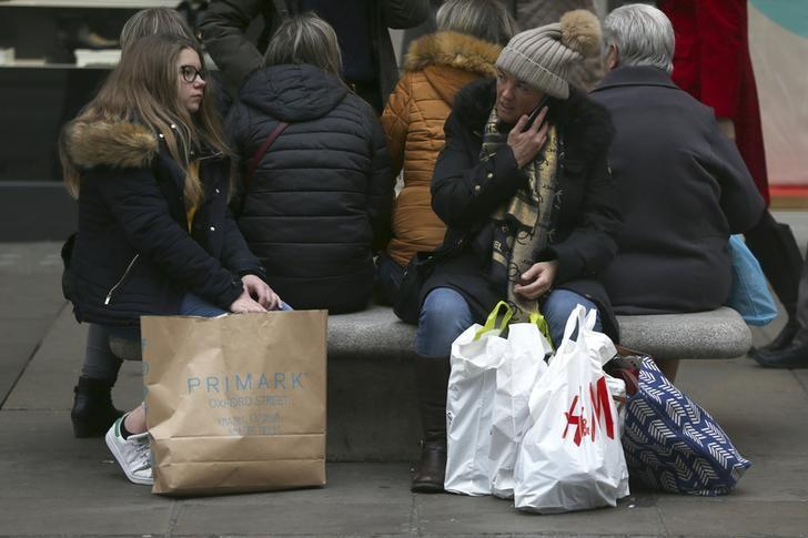 Shoppers rest on a bench with their bags on Oxford Street in London
