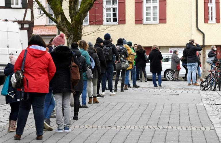 Outside Tuebingen's picturesque city hall people queue for Covid tests