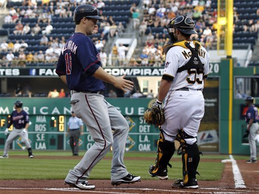 Minnesota Twins' Josh Willingham, left, scores in front of Pittsburgh Pirates catcher Michael McKenry on a single by Trevor Plouffe in the first inning of a baseball game on Wednesday, June 20, 2012, in Pittsburgh. (AP Photo/Keith Srakocic)