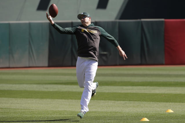 Oakland Athletics pitcher Homer Bailey catches a football during baseball practice in Oakland, Calif., Tuesday, Oct. 1, 2019. The Athletics are scheduled to face the Tampa Bay Rays in an American League wild-card game Wednesday, Oct. 2. (AP Photo/Jeff Chiu)