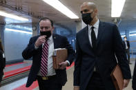 Sen. Mike Lee, R-Utah, left, and Sen. Cory Booker, D-N.J., right, walk on Capitol Hill in Washington, Thursday, Feb. 11, 2021, before the start of the third day of the second impeachment trial of former President Donald Trump. (AP Photo/Susan Walsh)
