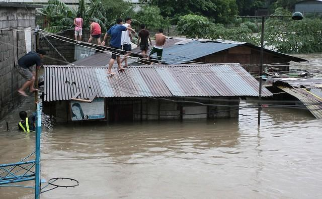 Flood victims stay on the rooftops of their homes in North Fairview near swollen Tullahan River, Quezon City, north of Manila, on Tuesday 07 August 2012. Continuous heavy monsoon rains since Sunday have left Metro Manila and nearby provinces flooded. (Mike Alquinto, NPPA Images)