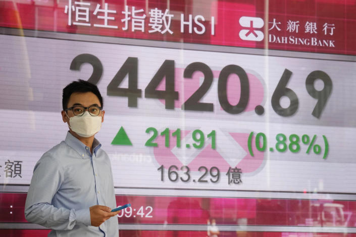 A man wearing a face mask walks past a bank's electronic board showing the Hong Kong share index in Hong Kong, Tuesday, Sept. 28, 2021. Asian shares mostly fell Tuesday as concerns about China chipped away at investor optimism following a mixed finish on Wall Street. (AP Photo/Kin Cheung)