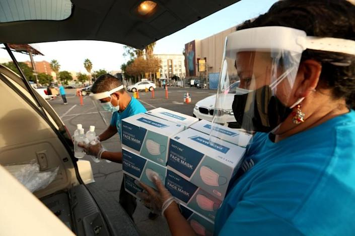 "HOLLYWOOD, CA - DECEMBER 26, 2020 - Gisela Mora, right, and Miguel Gonzalez, both with PPE Unite, load up a car with free masks, bottles of hand sanitizers and other PPE materials for small business owners in a parking lot along Hawthorn Avenue in Hollywood on December 26, 2020. PPE Unite, the L.A. County Department of Workforce Development, Aging and Community Services, the Los Angeles Small Business Development Center network and the Hollywood Chamber of Commerce handed out PPE materials to help protect small businesses in Los Angeles County to stay protected and open for business with a FREE 30-day supply of PPE. ""As businesses face adversity with the on-going health and economic crisis, our goal is to ensure that businesses don't have further burdens to their bottom line with the purchasing of PPE materials during this pandemic crisis,"" said Jay Taso, CEO of Logisticom and Co-Lead at PPE Unite. ""Through this collaborative partnership with the Hollywood Chamber of Commerce, businesses in the Hollywood area will receive the necessary supplies to help them to create a safe work environment."" To date, PPE Unite has signed up more than 750 businesses for this weekend's one-day event in Hollywood and over 25,000 small businesses since the launch of this initiative. Additionally, 4 million units of PPE masks and over 500,000 units of sanitizer have already been distributed since the launch of this initiative two months ago. (Genaro Molina / Los Angeles Times)"