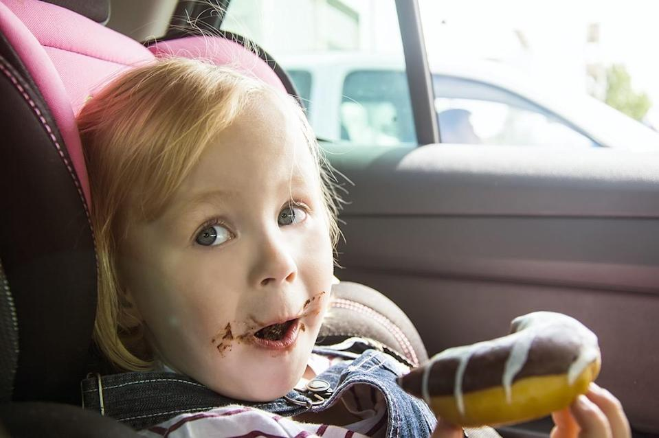 little girl eating chocolate donuts in car