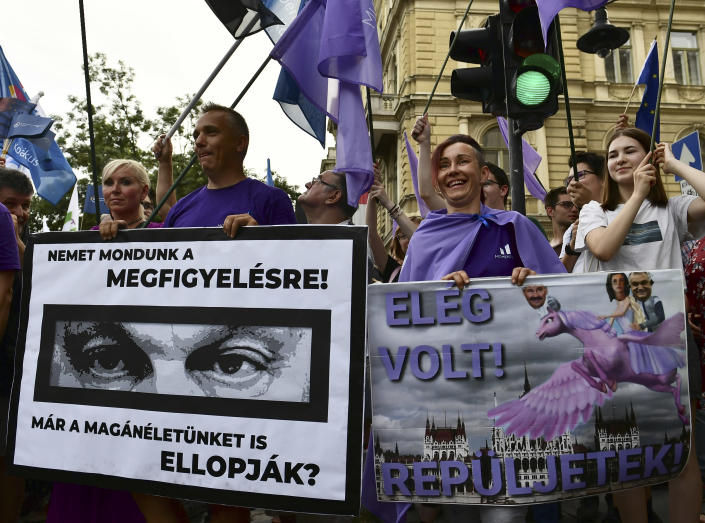 """People hold banners show Hungarian Prime Minister Viktor Orban, reading: """"We have to say no for observation!'' and ''Do they already stole our private life?"""", left, and """"It was enough! Fly!"""" during a protest against the government's alleged use of powerful spyware to spy on opponents, Budapest, Hungary, July 26, 2021. A report released more than a week ago by investigative journalists suggested the government used the software to monitor critical journalists, politicians and businesspeople through their smartphones. (AP Photo/Anna Szilagyi)"""