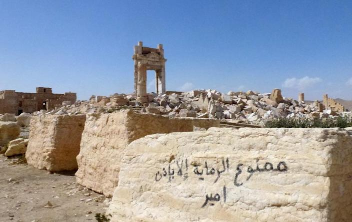 """Graffiti on a stone near the remains of the entrance to the iconic Temple of Bel that was destroyed by Islamic State in Palmyra, reads: """"Smoking is banned without the permission of the leader"""" (AFP Photo/Maher Al Mounes)"""