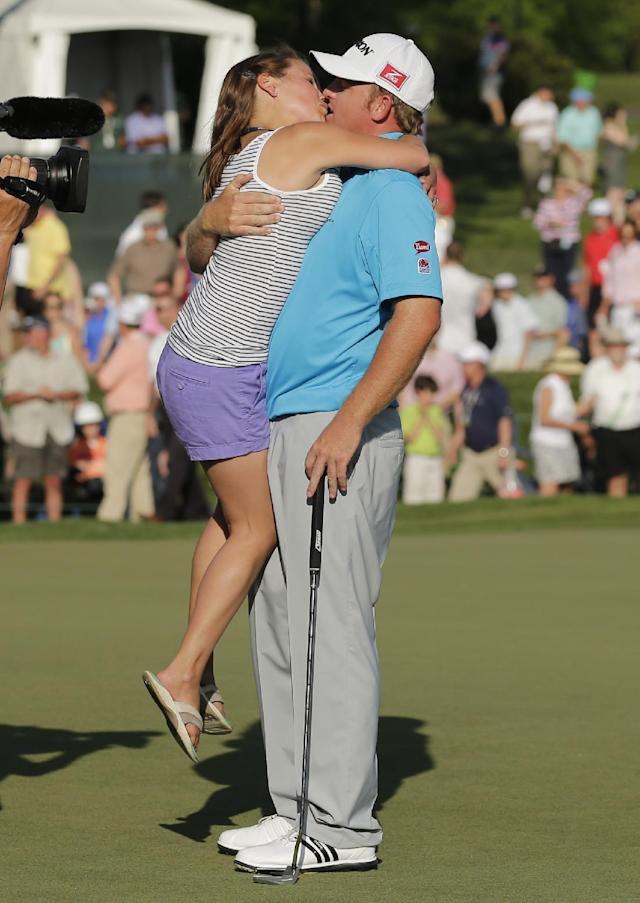 J.B. Homes, right, kisses his wife Sara, left, after winning during the Wells Fargo Championship golf tournament in Charlotte, N.C., Sunday, May 4, 2014. (AP Photo/Chuck Burton)