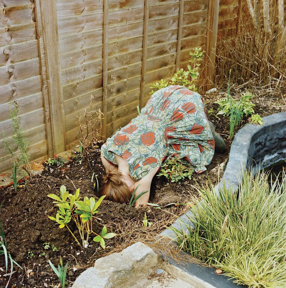 """<br><strong>""""Head in Hole"""" by Dulcie Wagstaff </strong><br><br><em>To help with her depression, Dulcie Wagstaff works in her garden. On this winter's day, she confronted the cold with a summery floral dress and imagined burying herself, """"connecting with the earth whilst hiding from the world above"""". She says: """"Gardening in winter is a defiant act, against the elements and our human instinct to stay indoors in the short, dark days. However in this instance it is a lifeline, in search of light, connection, movement and purpose.""""</em><span class=""""copyright"""">Photographed by Dulcie Wagstaff </span>"""