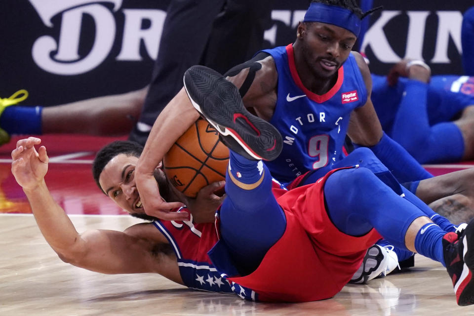Philadelphia 76ers guard Ben Simmons and Detroit Pistons forward Jerami Grant battle for the loose ball during the second half of an NBA basketball game, Saturday, Jan. 23, 2021, in Detroit. (AP Photo/Carlos Osorio)