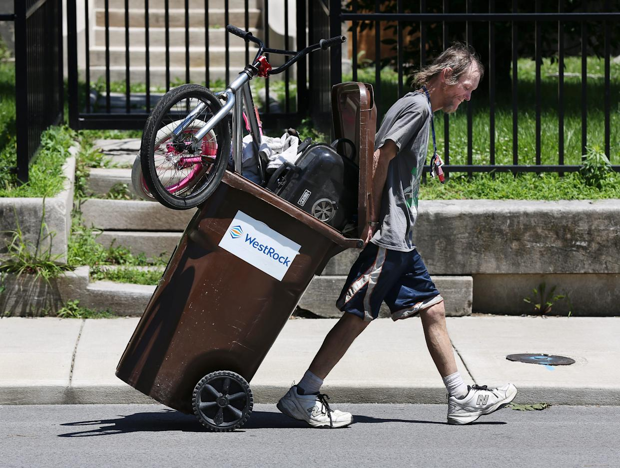"""Brent Spradlin transports an array of items he has collected around downtown in a recycling waste receptacle as he walked down Brook Street on his way to a homeless camp. The city has posted """"No Trespassing"""" signs beneath the I-65 overpass at Brook and Breckinridge where he lives. They have given the people living there three weeks notice that the camps will be removed. June 25, 2019"""