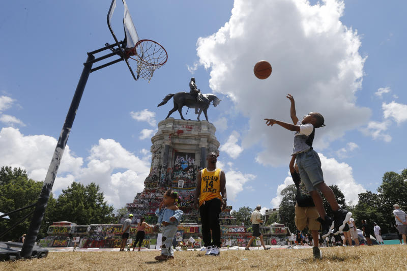 Isaiah Bowen, right, takes a shot as his dad, Garth Bowen, center, looks on at a basketball hoop in front of the statue of Confederate General Robert E. Lee on Monument Avenue Sunday June 21, 2020, in Richmond, Va. A judge extended an injunction delaying the removal of the statue by the state. The statue had become a focal point for the Black Lives Matter movement in Richmond. (AP Photo/Steve Helber)