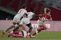 Britain's Abbie Brown, right, takes off with the ball, pursued by Cheta Emba and Abby Gustaitis of the United States, in their women's rugby sevens quarterfinal match at the 2020 Summer Olympics, Friday, July 30, 2021 in Tokyo, Japan. (AP Photo/Shuji Kajiyama)