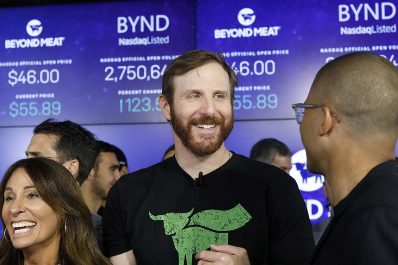 FILE - In this May 2, 2019, file photo Beyond Meat CEO Ethan Brown, center, watches as his company's stock begins to trade following its IPO at Nasdaq in New York. Plant-based meat maker Beyond Meat beat Wall Street's expectations in its first earnings report since its IPO last month. The El Segundo, California-based company lost $6.6 million, or 95 cents per share, in the first quarter, up slightly from a 98-cent loss in the same period a year ago. (AP Photo/Mark Lennihan, File)