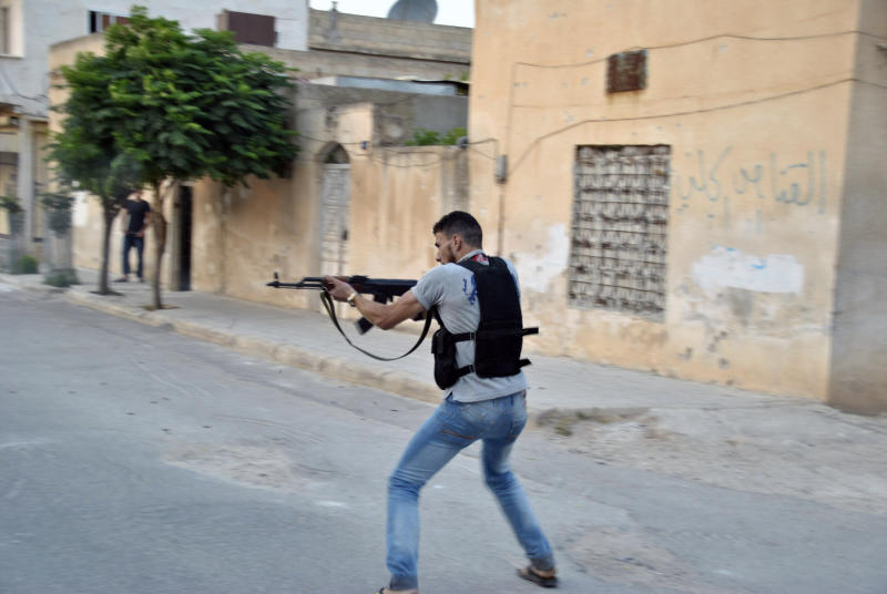 In this Sunday, 22 July, 2012 photo a Syrian rebel fires his weapon during clashes with Syrian troops in Idlib, Syria. (AP Photo/Fadi Zaidan)