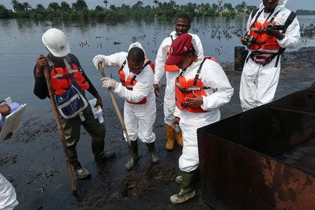 Members of the joint task force, part of the Bodo oil spill clean-up operation, inspect the site of an illegal refinery near the village of Bodo in the Niger Delta, Nigeria August 2, 2018. REUTERS/Ron Bousso/Files