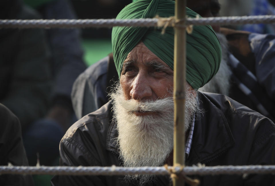 an Indian farmer listens to speech of a fellow farmer as they block a highway in protest against new farm laws at the Delhi-Uttar Pradesh state border, on the outskirts of New Delhi, India, Wednesday, Dec. 30, 2020. Protesting farmers fear the government will stop buying grain at minimum guaranteed prices and corporations will then push down prices. The government says the three laws approved by Parliament in September will enable farmers to market their produce and boost production through private investment. (AP Photo/Manish Swarup)AP Photo/Manish Swarup)